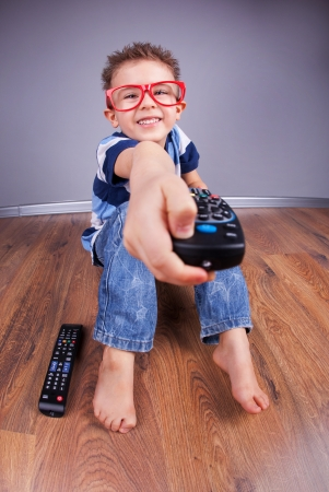 Cheerful child with tv remote control  photo