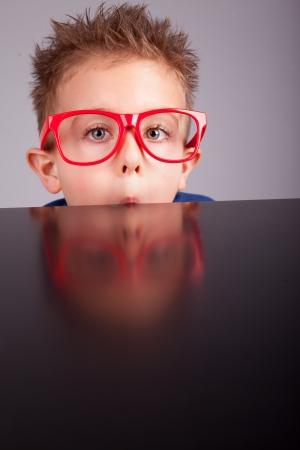 five years old: Cinque anni ragazzo carino nascondersi dietro un tavolo