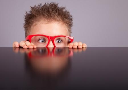 Cinco años chico lindo poco escondido detrás de una mesa