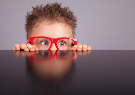 Five years old little cute boy hiding behind a table  Stock Photo