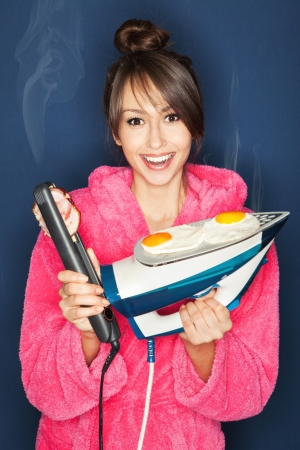 kitchen appliances: Beautiful young woman frying eggs and bacon on an iron and hair straightener