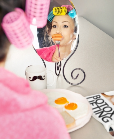 augmentation: Woman with sausages on a fork simulating lip enhancement while having breakfast  Stock Photo