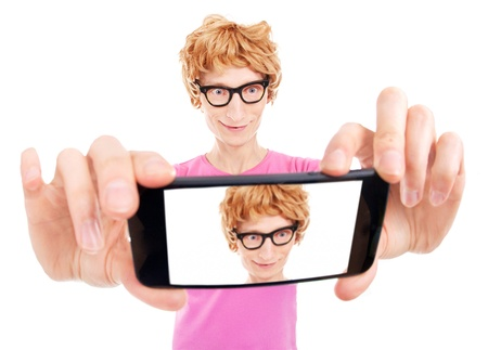Funny nerdy guy is taking a self portrait with a smart phone photo
