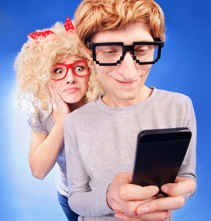 afraid man: Girl is spying on boyfriend he is using a smart phone  Stock Photo