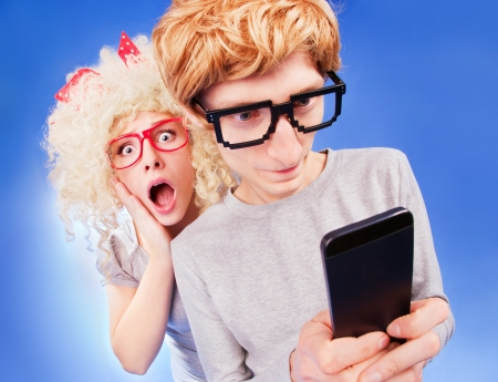he: Girl is spying on boyfriend he is using a smart phone  Stock Photo
