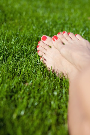 painted toes: Painted red toes on green grass Stock Photo