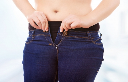 unzip: Size 40 42 woman zipping tight jeans, obesity and overweight concept  Stock Photo