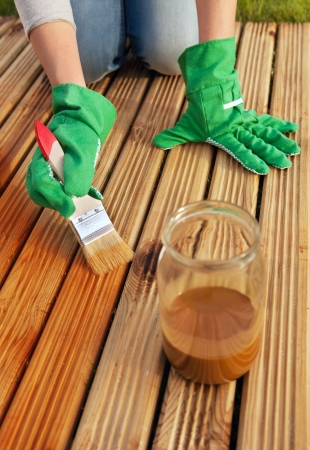 treated board: Applying protective varnish on a patio wooden floor