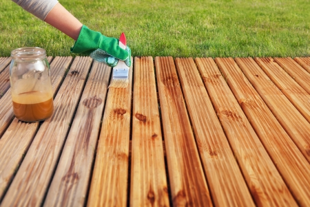 Applying protective varnish on a patio wooden floor  photo