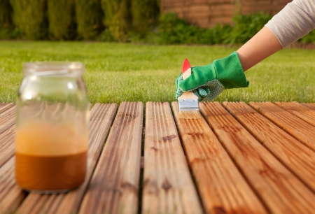 decking: Applying protective varnish on a patio wooden floor