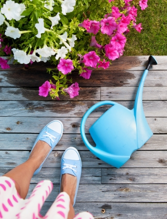 Woman with watering can and flowers on a patio deck photo