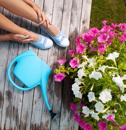 patio deck: Donna con annaffiatoio e fiori su un mazzo patio