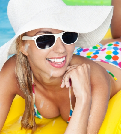 young girl bikini: Young happy woman relaxing in a swimming pool