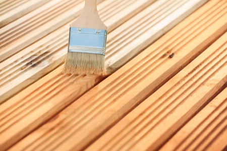 staining: Applying protective varnish on a wooden furniture