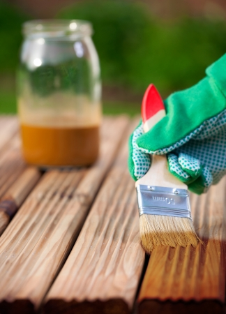 staining: Applying protective varnish on a patio wooden floor