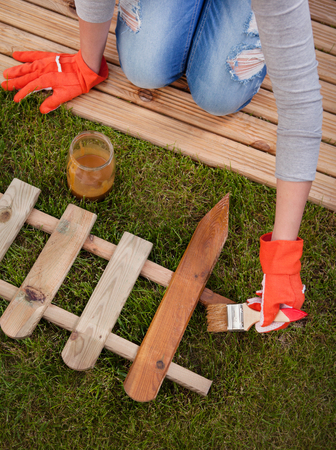 treated board: Applying protective varnish to a wooden fence