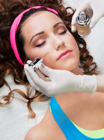 serum: Woman getting face treatment in medical spa center Stock Photo
