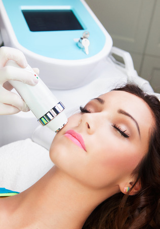 dermatology: Woman getting laser face treatment in medical spa center
