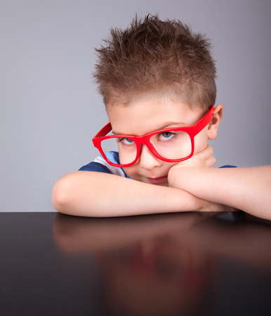 Sad bored five years old boy wearing glasses photo