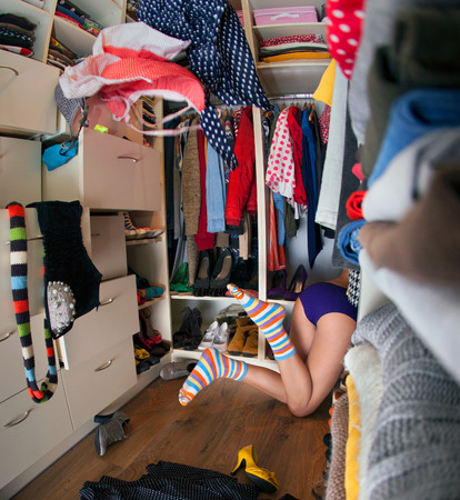 messy clothes: Nothing to wear concept, young woman searching for clothing in walk in closet