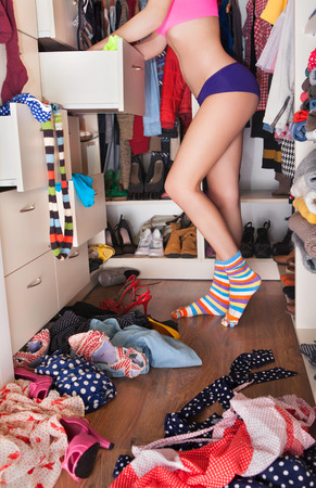 Getting dressed concept woman wearing underwear in walk in closet choosing clothes photo