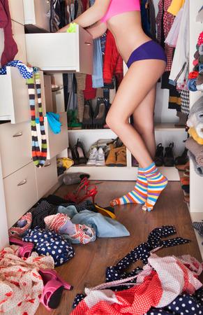 levantandose: Primeros concepto de la mujer vestida con ropa interior en el vestidor que elige la ropa Foto de archivo