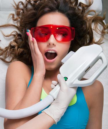 esitazione: Donna che ottiene trattamento laser viso nel centro termale medico, espressione divertente, esitazione, il concetto del dolore