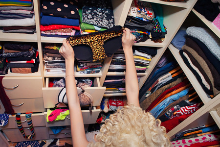 woman closet: Getting dressed concept woman in walk in closet choosing underwear  Stock Photo