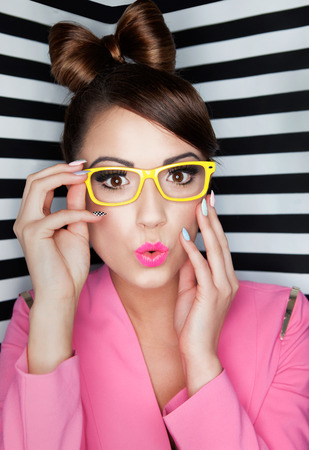 funny glasses: Attractive young surprised woman wearing glasses on stripy background, beauty and fashion concept  Stock Photo