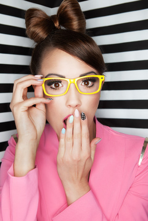 wayfarer: Attractive young surprised woman wearing glasses on stripy background, beauty and fashion concept  Stock Photo