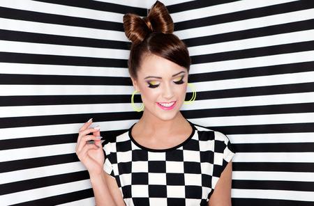 aretes: Mujer joven y atractiva sobre fondo de rayas, la belleza y el concepto de moda