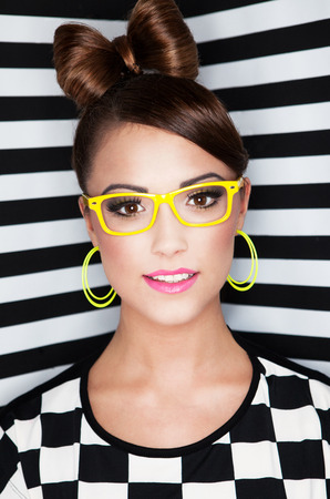 Attractive young woman wearing glasses on stripy background, beauty and fashion concept  photo