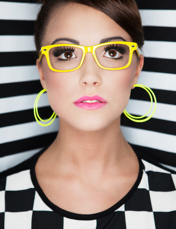 girl glasses: Attractive young woman wearing glasses on stripy background, beauty and fashion concept