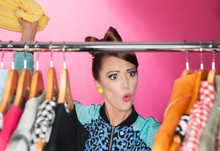 Tijd voor verfrissende garderobe jonge aantrekkelijke verraste vrouw op zoek naar kleding in een kast