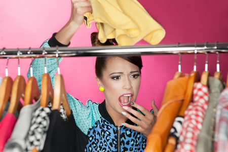 choose person: Time for refreshing wardrobe young attractive surprised woman searching for clothing in a closet