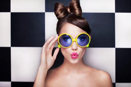 Aantrekkelijke verrast jonge vrouw draagt een zonnebril op geruite achtergrond, schoonheid en mode-concept