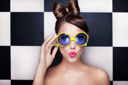 beautiful girl face: Attractive surprised young woman wearing sunglasses on checkered background, beauty and fashion concept