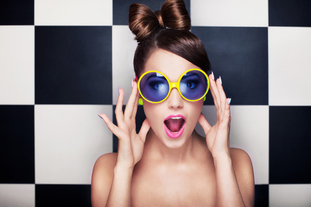 fashion: Attractive surprised young woman wearing sunglasses on checkered background, beauty and fashion concept