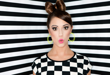 Attractive surprised young woman on stripes wallpaper background, beauty and fashion concept  photo