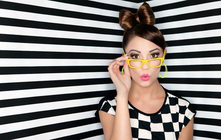 bollos: Atractiva mujer joven sorprendido usar lentes sobre fondo a cuadros, la belleza y el concepto de moda Foto de archivo