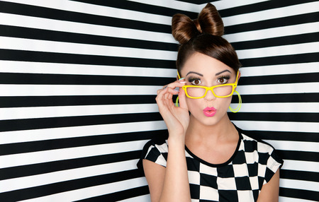 glam: Attractive surprised young woman wearing glasses on checkered background, beauty and fashion concept
