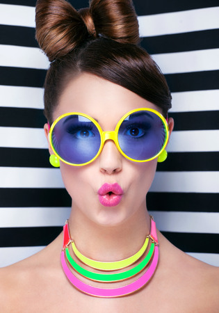 Attractive surprised young woman wearing sunglasses on striped background, beauty and fashion concept  Stock Photo