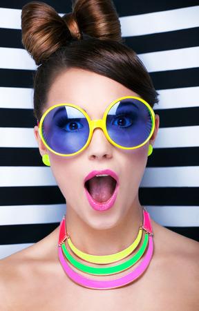 �tonnement: Attractive jeune femme surprise portant des lunettes de soleil sur fond ray�, la beaut� et le concept de mode