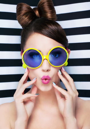 Attractive surprised young woman wearing sunglasses on striped background, beauty and fashion concept  photo