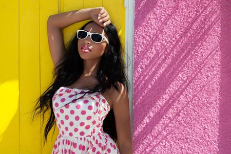 Aantrekkelijke jonge Afro-Amerikaanse vrouw draagt een zonnebril