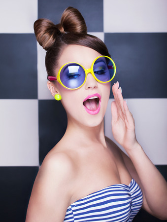 expressive face: Attractive surprised young woman wearing sunglasses on checkered background, beauty and fashion concept