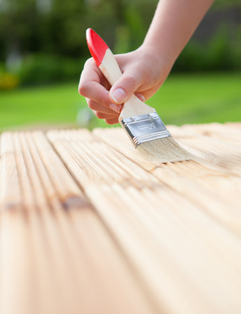 treated board: Hand with brush on a wooden background