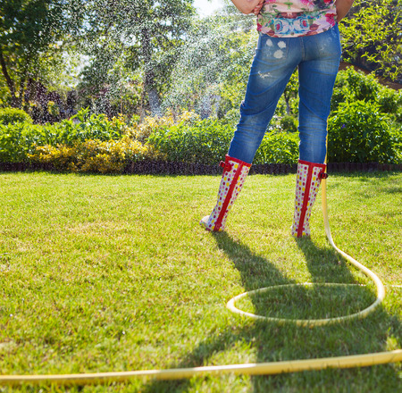 Woman holding garden water hose wearing colorful wellies watering garden  photo