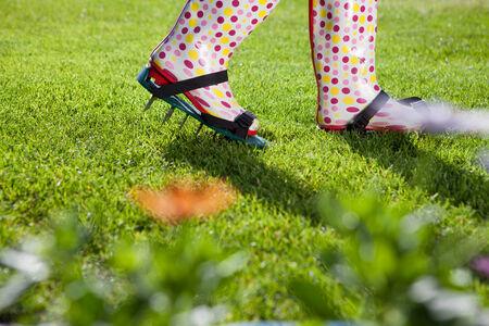 �spiked: La mujer llevaba c�sped pinchos revitalizar airear zapatos, concepto de jardiner�a