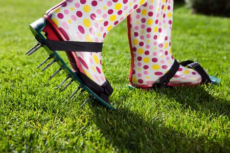 �spiked: La mujer llevaba c�sped pinchos revitalizar zapatos de aireaci�n, el concepto de la jardiner�a Foto de archivo